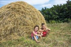 In de zomer dichtbij de hooiberg is er een mooie landelijke jongen w Royalty-vrije Stock Foto's
