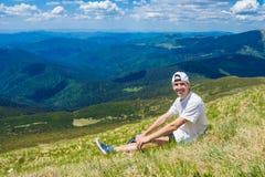 De zomer die in de bergen wandelen De jonge toeristenmens in een GLB met handen op de bovenkant van de bergen bewondert omhoog de Royalty-vrije Stock Foto's