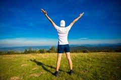 De zomer die in bergen wandelen De jonge toeristenmens in GLB met handen bovenop bergen bewondert omhoog aard stock fotografie