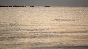De zomer eerste licht vóór zonsopgang boven zwarte rotsen door de overzeese kusten stock footage