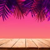 De zomer en aardproductvertoning met houten lijstteller op palmblad op trillende kleurenachtergrond stock foto