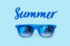 De zomer geweven blauwe tekst en blauwe die zonnebril met palmenbezinningen op een lichtblauwe achtergrond worden geïsoleerd stock foto