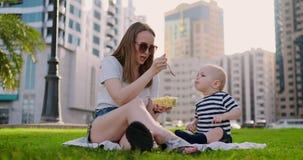 In de zomer in het Park voedt het mamma het kind van de containerlunch stock videobeelden