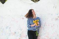 De zomer jonge vrouw in gestript vest met trillend boeket van gele fresia's en irissen dichtbij lichte concrete muur stock fotografie