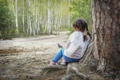 In de zomer, leunt een kleine engel tegen een boom in het bos royalty-vrije stock foto