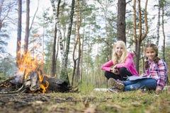 In de zomer in de middag dichtbij een brand twee gelukkige meisjes van Th stock afbeelding