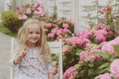 De zomer Moeders of van vrouwen dag Meisje bij bloeiende bloem De Dag van kinderen Klein babymeisje enkel Geregend Kinderjaren royalty-vrije stock afbeelding