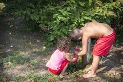 In de zomer, op een hete dag in de straat, twee jonge kinderen, een bro Royalty-vrije Stock Foto's