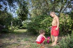 In de zomer, op een hete dag in de straat, twee jonge kinderen, een bro Stock Afbeelding