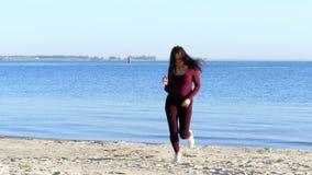 In de zomer, op de rivierbank, op het strand bij dageraad, een mooie vrouwenkunstenaar, in een strak kostuum, danst zij, springt stock videobeelden