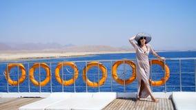 De zomer, overzees, mooie jonge donkerbruine vrouw, in een lange kleding en zonnebril, bevindt zich op het dek van een veerboot,  stock videobeelden