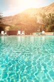De zomer, Reis, Vakantie en Vakantieconcept De zitkamer zit dichtbij zwembad voor tegen Judean-Woestijn Turkooise pool royalty-vrije stock foto