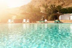 De zomer, Reis, Vakantie en Vakantieconcept De zitkamer zit dichtbij zwembad voor tegen Judean-Woestijn Turkooise pool royalty-vrije stock foto's