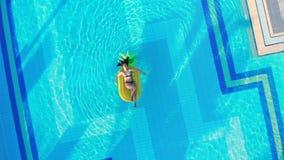 De zomer reizend concept De jonge vrouw ontspant op een gele matras, die in een pool drijven stock footage