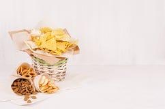 De zomer snel voedsel - verschillende knapperige snacks in rieten rustieke mand en ambachtdocument kornet op zachte witte houten  stock foto