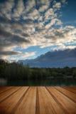 De zomer trillende die zonsondergang in kalme meerwateren wordt weerspiegeld met houten Royalty-vrije Stock Afbeeldingen
