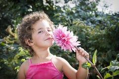 In de zomer in de tuin, snuift een klein grappig krullend meisje l Stock Foto's