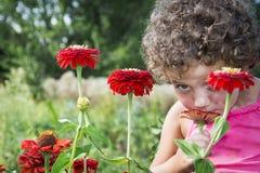 In de zomer in de tuin, snuift een klein grappig krullend meisje l Stock Fotografie