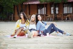 De zomer, vakantie, vakantie en gelukconcept - groep jonge aantrekkelijke vrouwenvrienden op het strand stock afbeeldingen
