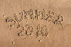 De zomer van 2016 geschreven op het zand in de stralen van de zon Stock Afbeelding