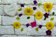 De zomer van de teken 'I liefde 'op het hart tegen een witte bakstenen muur en vele kleine bloemen stock fotografie
