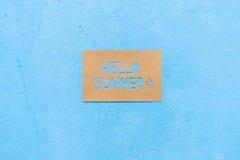De Zomer van teksthello op papier met blauwe achtergrond Stock Afbeeldingen