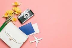 De zomerachtergrond Vrouwelijke handtas, een boeket van bloemen, een camera, een vliegtuigkaartje en een stuk speelgoed vliegtuig royalty-vrije stock afbeeldingen