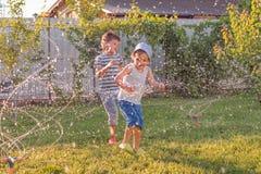 De zomeractiviteiten Kinderen spelen openlucht met automatisch installatie het water geven systeem Glimlachende jongen die pret h royalty-vrije stock afbeeldingen