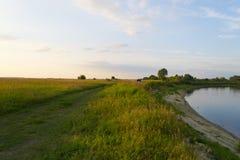 De zomeravond op de bank van een rivier Stock Foto