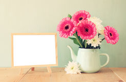 De zomerboeket van bloemen op de houten lijst en het bord met ruimte voor tekst met muntachtergrond wijnoogst gefiltreerd beeld stock foto