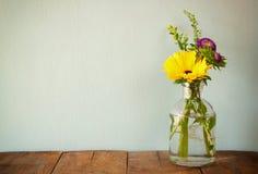 De zomerboeket van bloemen op de houten lijst met muntachtergrond wijnoogst gefiltreerd beeld stock foto