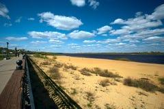 De zomercityscape met zandige kust van rivier Royalty-vrije Stock Afbeeldingen