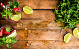 De zomercocktails van aardbeimojito met munt en kalk in glazen Stock Foto's