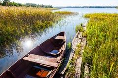 De zomerdag op het meer met een het roeien boot op de kust Stock Afbeeldingen