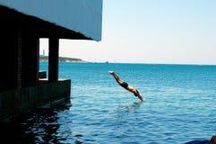 De zomerdag op zee, duikt een mens van de pijler in het overzees stock foto