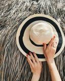 De zomerhoed met handen Vlakte van manicure lag de rode spijkers Royalty-vrije Stock Afbeeldingen