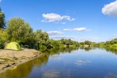 De zomerkamp op de banken van de Desna-rivier, de Oekraïne Spinnende staven en een tent op het strand royalty-vrije stock foto