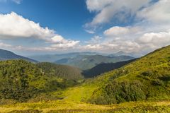 De zomerlandschap in bergen en de donkerblauwe hemel met wolken Stock Foto