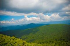 De zomerlandschap in bergen en de donkerblauwe hemel met wolken Royalty-vrije Stock Fotografie