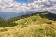 De zomerlandschap in bergen en de donkerblauwe hemel met wolken Stock Foto's