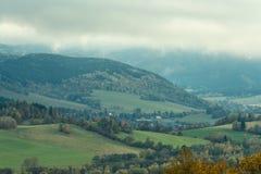 De zomerlandschap en de donkerblauwe hemel met wolken in bergen Stock Foto