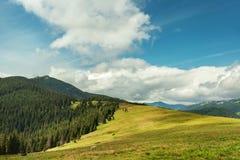 De zomerlandschap in Karpatische bergen en de blauwe hemel met wolken Stock Fotografie