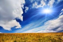 De zomerlandschap met gebied van gras, blauwe hemel en zon Stock Afbeelding