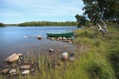 De zomerlandschap met groene boot bij het meer Stock Foto's