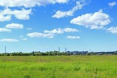 De zomerlandschap met veel weg gebied van gras en industriële voorwerpen Stock Fotografie