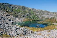 De ZOMERlandschap Mooie bergen en een bergmeer tegen de blauwe hemel vallei stock foto's