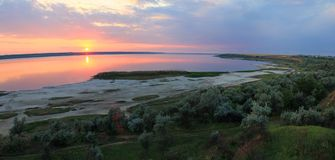 De zomerlandschap op de banken van het meer bij zonsondergang stock foto's