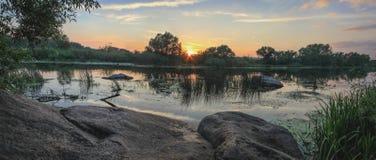 de zomerlandschap op de banken van de rivier bij zonsondergang stock foto