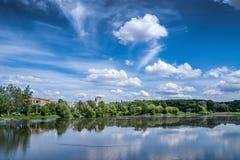 De zomerlandschap: de witte wolken in blauwe hemel worden weerspiegeld in pur Stock Fotografie