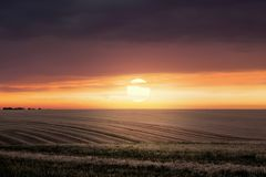 De zomerlandschap: zonsondergang op het gebied, donkere wolken bij top_ Royalty-vrije Stock Foto's